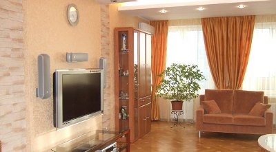 Contemporary-living-room-with-wood-floor-cream-walls-and-drapery-and-brown-sofa-set